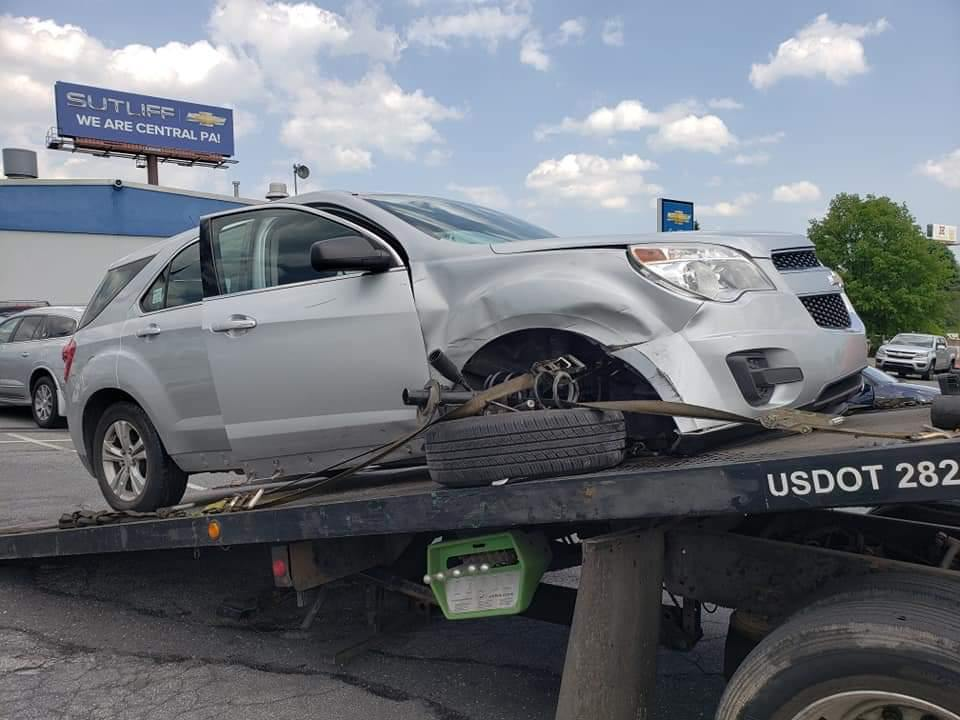 Image of a car that has been in an accident being towed on a flatbed wrecker truck.