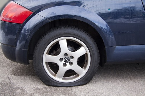 A picture of a car with a flat tire that needs repairing in Lancaster.