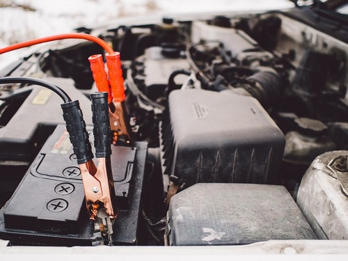 Picture of a car engine with jumper cables hooked up to the battery to give it a jumpstart.