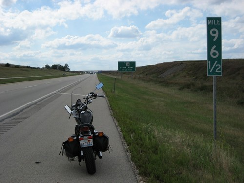 A picture of a motorcycle stuck on the side of the road that needs to be towed.
