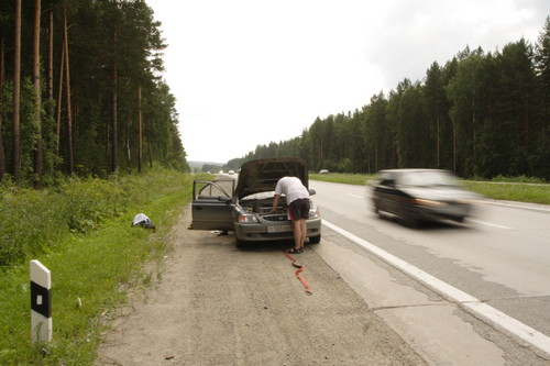 A picture of a car broken down on the side of the road.